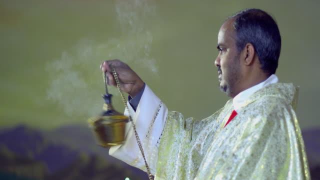 vídeos de stock e filmes b-roll de ms priest blessing altar with incense, manhattan beach, california, usa - benção