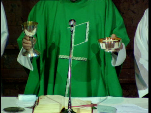 Priest consecrates bread and wine during Mass in Catholic church Basque Country Spain