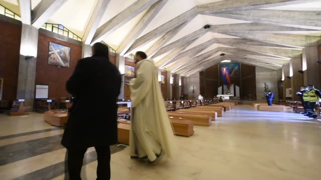 priest don marcello gives a blessing to the coffins of deceased people inside the church of san giuseppe in seriate, on march 28, 2020. because of... - italien stock-videos und b-roll-filmmaterial