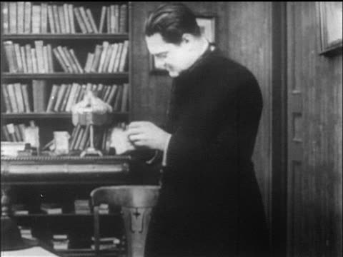 b/w 1912 priest (lionel barrymore) enters room + sits while reading letter - priest stock videos & royalty-free footage