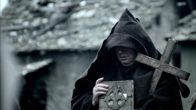 vidéos et rushes de a priest gives final rights and blessings upon burning corpses during the black plague. - prêtre