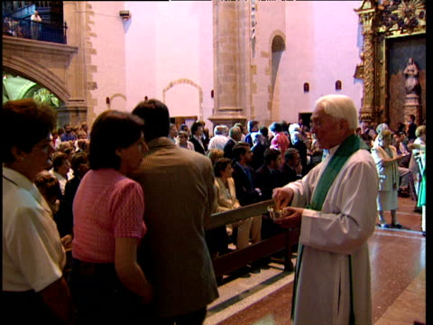 Priest gives out consecrated bread in Catholic church as worshippers sing Basque Country Spain