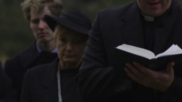 priest giving a eulogy at a funeral - trauerzeit stock-videos und b-roll-filmmaterial