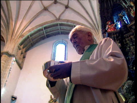 Priest hands out consecrated bread in Catholic church as worshippers sing Basque Country Spain