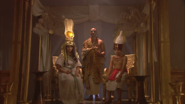 A priest in a leopard skin robe holds incense as he leads Egyptian royalty away from a throne.