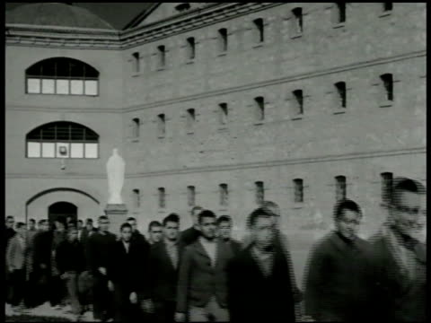 vídeos de stock e filmes b-roll de priest leading line of prisoners through courtyard catholic prisoners standing in chapel crossing themselves priest standing in front of talking to... - padre