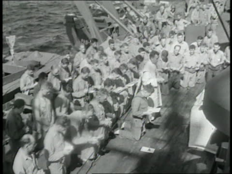 priest leads a group of soldiers in prayer on the deck of a ship. - 船の一部点の映像素材/bロール