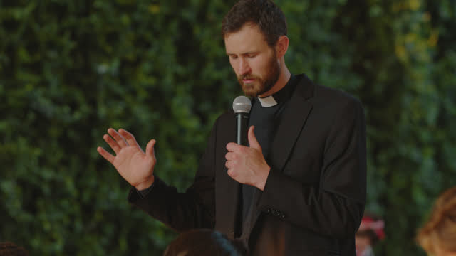 priest leads a newlywed couple in prayer to bless both the food and their marriage - priest stock videos & royalty-free footage