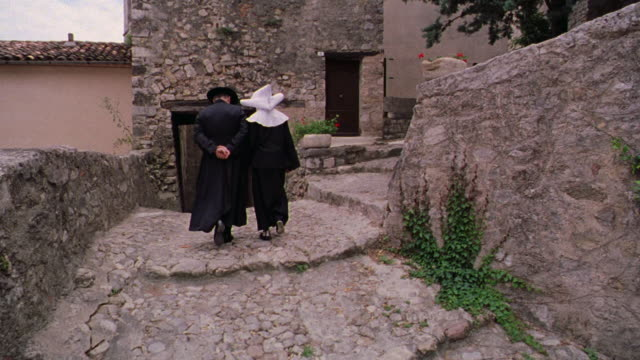vídeos de stock e filmes b-roll de rear view priest + nun walking on cobblestone sidewalk away from camera / seillans, provence, france - padre