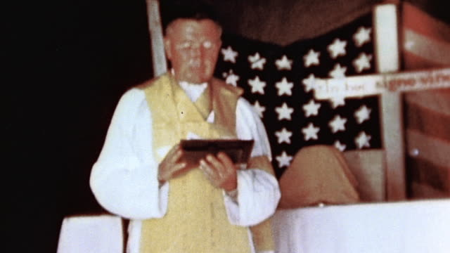 vidéos et rushes de priest performing service before makeshift altar, american flag and simple wooden cross behind - prêtre