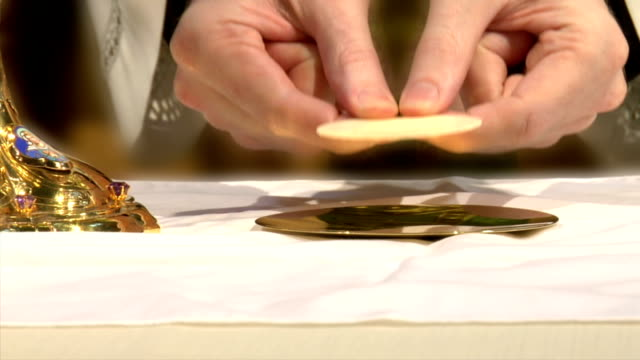 stockvideo's en b-roll-footage met priest places eucharist on plate - katholicisme