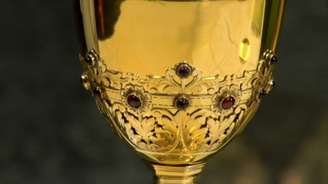 Priest pouring water and wine into a chalice