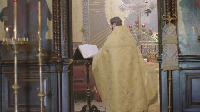 vídeos de stock e filmes b-roll de ms priest praying in church with bible in front of altar - padre