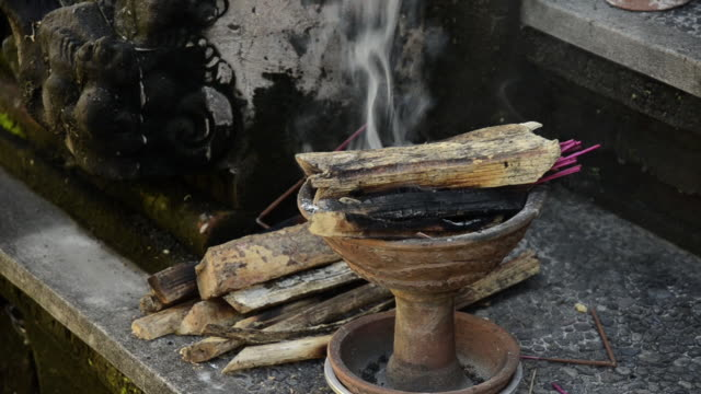 ms priest putting firewood on burning incense in vessel in pura dalem puri temple / ubud, bali, indonesia - incense stock videos & royalty-free footage