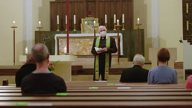 priest reading bible in cathedral during covid-19 - pastor stock videos & royalty-free footage