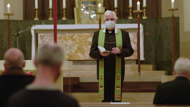 priest reading bible in church during covid-19 - pastor stock videos & royalty-free footage