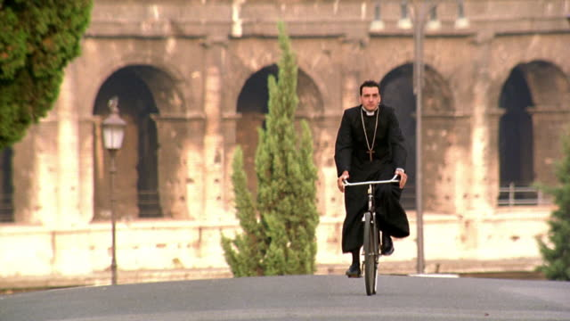 priest riding bicycle towards camera with colosseum in background / rome, italy - priest stock videos and b-roll footage