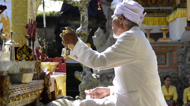 vídeos de stock e filmes b-roll de ms priest ringing bell and performing hindu ceremony in pura dalem puri temple / ubud, bali, indonesia - padre