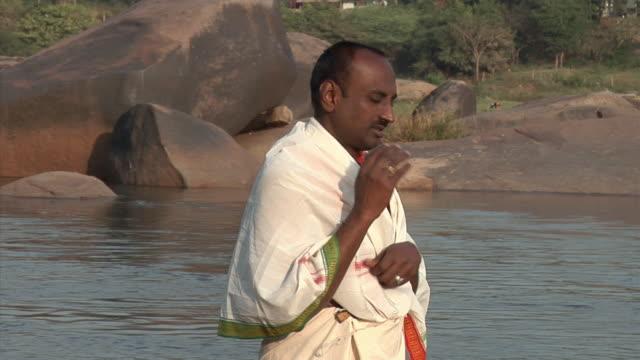 MS, Priest standing in water and praying, Hampi, Karnataka, India