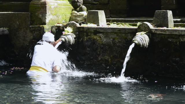 ms priest take bath in holy spring of pura tirta empul / tampaksiring, bali, indonesia - acqua santa video stock e b–roll
