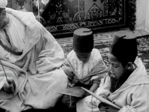 1934 b/w ms ha pan priest teaching young boys sitting on carpets on ground / rabat, morocco - rabat morocco stock videos & royalty-free footage
