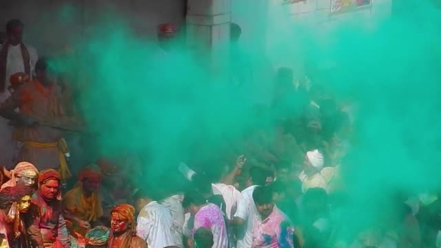 vídeos y material grabado en eventos de stock de priest throws dry colour onto the public / religious festivities and celebrations inside the temple complex in nandgaon mathura the village of lord... - krishna