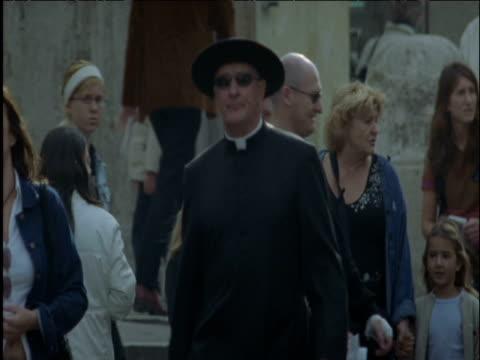 priest walks amongst crowd in street rome - 帽子点の映像素材/bロール