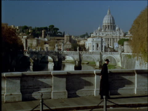 priest walks past st peter's basilica rome - テベレ川点の映像素材/bロール