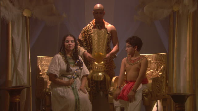 A priest wearing a leopard skin robe places a gold crown on a woman sitting next to a boy in a throne room.