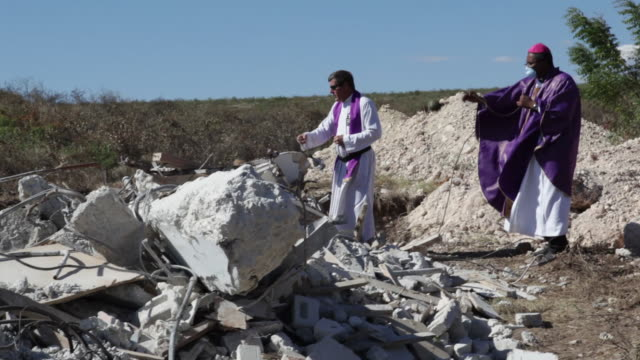 Priests bless earthquake victims covered by debris.