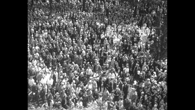 priests conduct outdoor mass for father louis hennepin next to bunting-festooned building, large crowd under trees in foreground / aerial pan large... - 1920 1929 stock videos & royalty-free footage