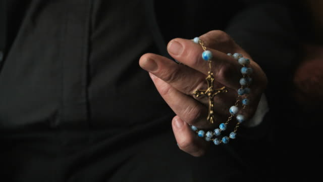 vidéos et rushes de cu priest's hand holding prayer beads, pasadena, california, usa - religion