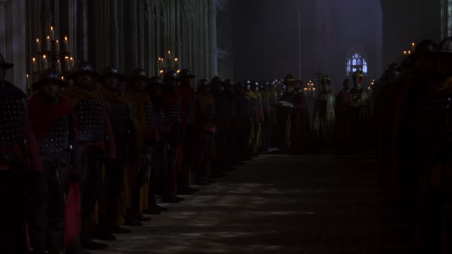 Priests pass out communion to a group of knights in a church.