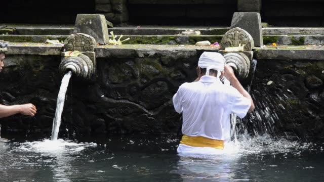 ms priests take bath in holy spring of pura tirta empul / tampaksiring, bali, indonesia - acqua santa video stock e b–roll