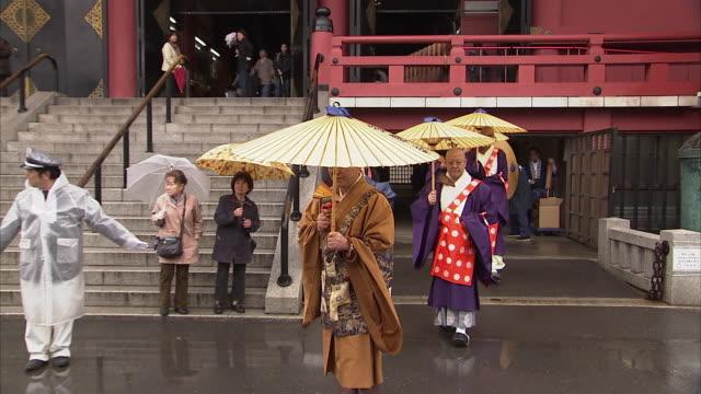 ws zo priests walking with umbrellas at senso ji temple, tokyo, japan - traditional clothing stock videos & royalty-free footage