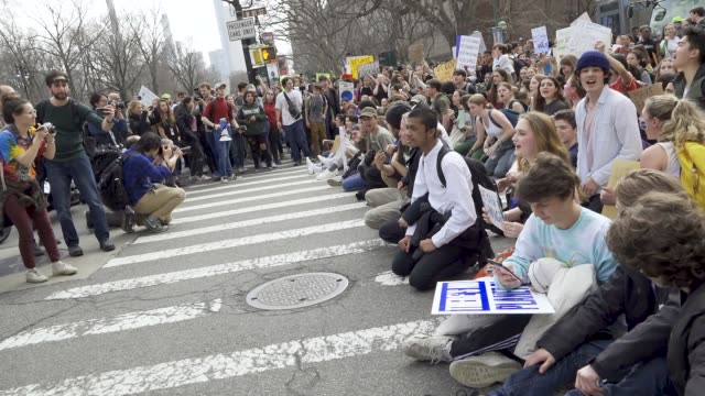 primarily high school teenagers stop vehicular traffic on west 79 and central park west by locking arms and forming a chain and by sitting on the... - individual event stock videos & royalty-free footage