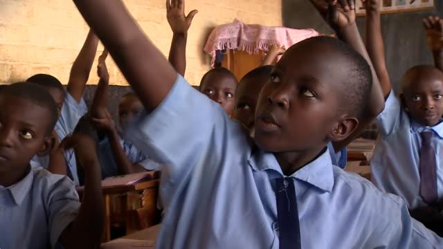 Primary school children and teacher in classroom in Rwanda