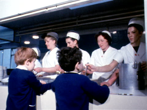primary school children queue up to receive their school dinners from the canteen staff 1969 - serving utensil stock videos and b-roll footage