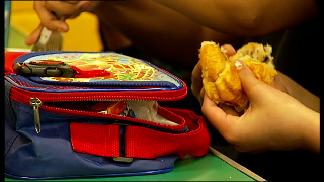vídeos de stock, filmes e b-roll de primary school makes controversial decision to remove junk food from children's packed lunches int hands putting items into lunchbox next packet of... - packed lunch