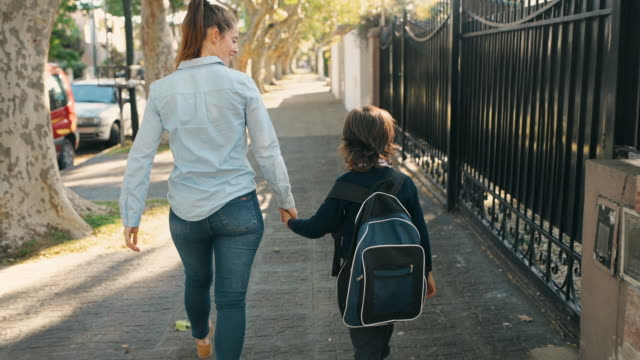 primary school student walking to school with mother - educazione video stock e b–roll