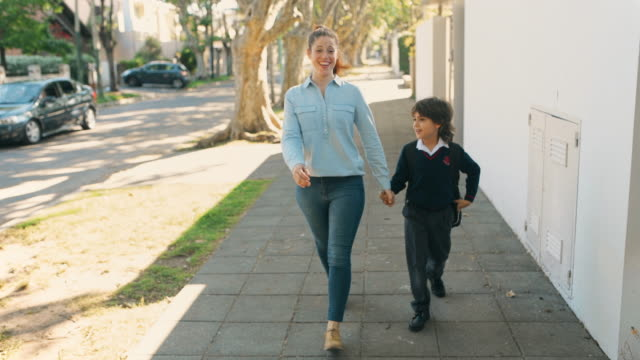 primary school student walking to school with mother - argentinian culture stock videos & royalty-free footage