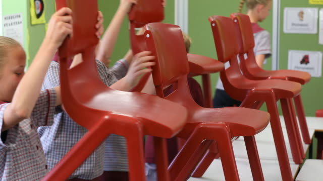 primary school students putting up chairs at the end of class - chair stock videos & royalty-free footage