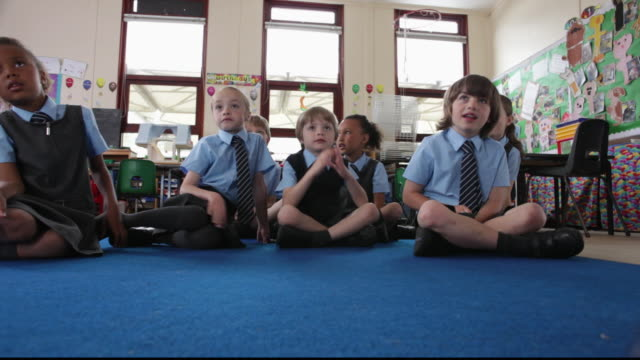 vídeos de stock e filmes b-roll de la primary school students sitting on classroom floor eagerly raising their hands / great yarmouth, england, united kingdom - sala de aula