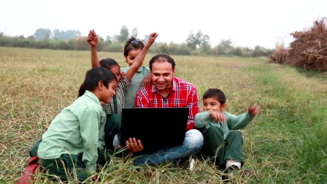 primary school students with teacher sitting in the field holding laptop - primary school child stock videos and b-roll footage