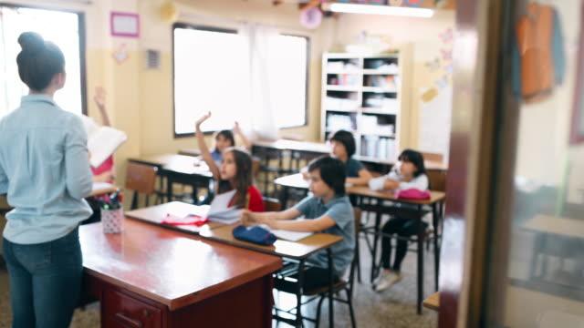 lågstadielärare som arbetar med elever i classroom - höjd hand bildbanksvideor och videomaterial från bakom kulisserna