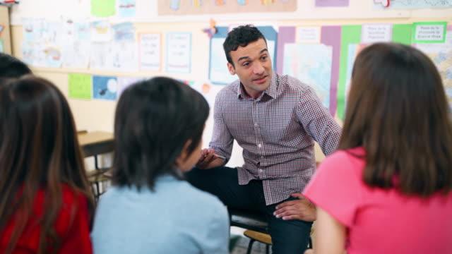 vídeos de stock, filmes e b-roll de professor da escola preliminar que trabalha com estudantes na sala de aula - argentina