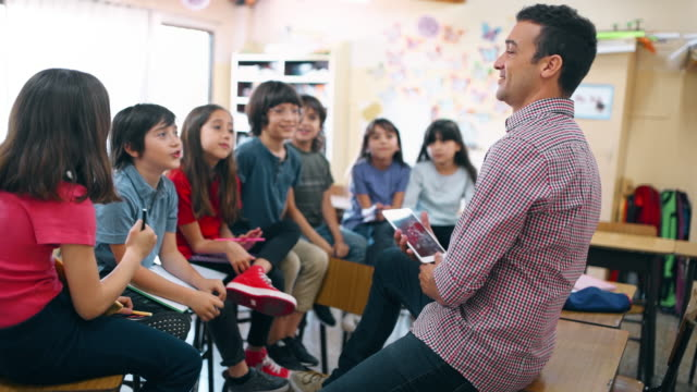 primary school teacher working with students in classroom - aula video stock e b–roll