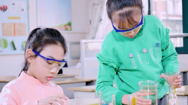 wissenschaft grundschüler experimentieren im klassenzimmer. - schutzbrille stock-videos und b-roll-filmmaterial