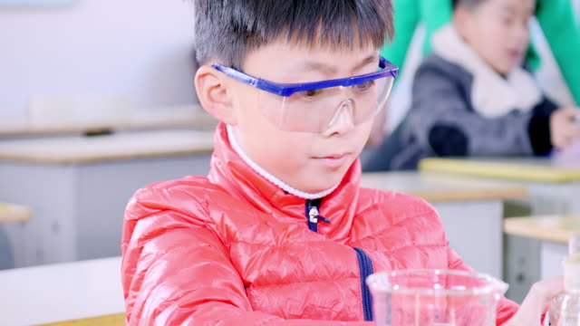 primary students doing science experiment in classroom. - safety glasses stock videos & royalty-free footage