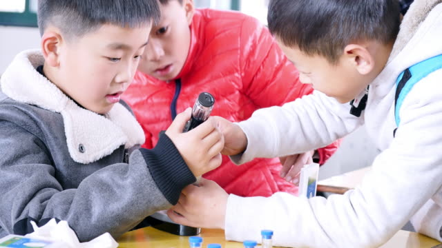 primary students doing science experiment in classroom.